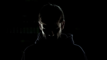 Silhouette of criminal regretting wrong decisions isolated on black background
