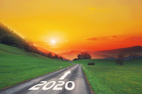 Empty asphalt road and New year 2020 concept. Driving on an empty road on goals in the mountains to upcoming 2020 and leaving behind old years. Concept for success, passing time and future.