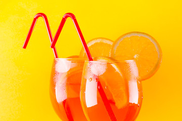 Cocktail aperol spritz on red yellow background. Summer alcoholic cocktail with orange slices....