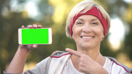 Sportive adult lady pointing at smartphone with green screen and smiling, app