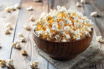 A wooden bowl of salted popcorn at the old wooden table. Dark background. selective focus