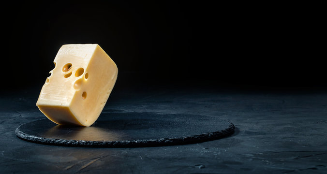 Delicious dutch cheese on dark background. Copy space