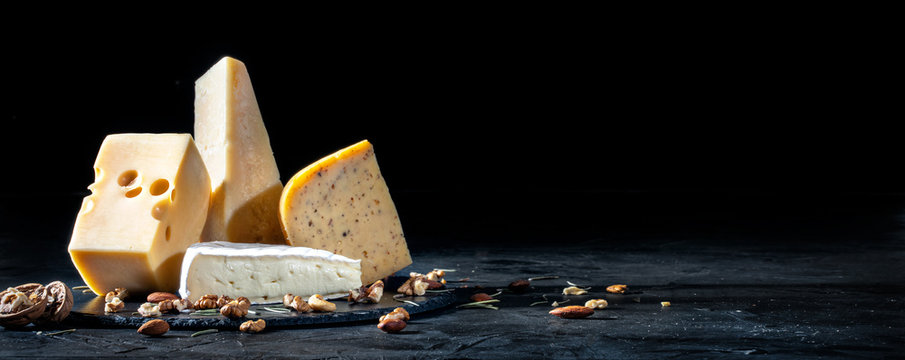 Different kinds of cheese with nuts on dark background, copy space