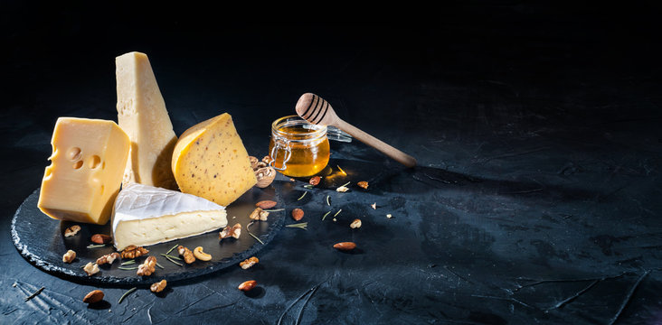 Different kinds of cheese with nuts and honey on dark background, copy space