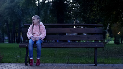 Sad school girl sitting on bench in park, lost missing kid, waiting for parents Wall mural