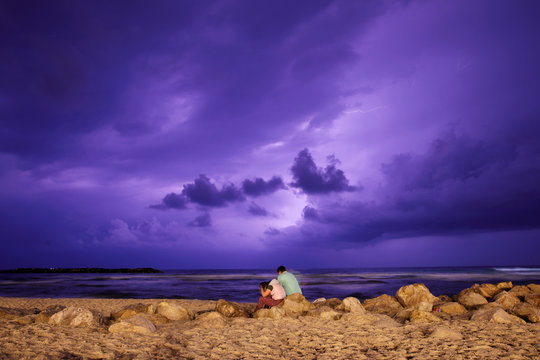 People are seen on the beach as lightning strikes over the Mediterranean at the city of Ashkelon