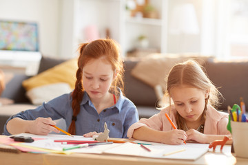 Portrait of two sisters drawing pictures together sitting at table at home lit by warm sunlight, copy space