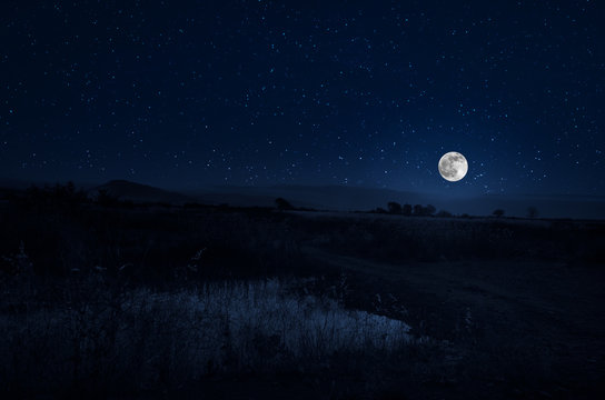 Mountain Road through the forest on a full moon night. Scenic night landscape of country road at night with large moon. Selective focus