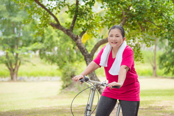 Beautiful aged asian woman riding bicycle for exercise in park,healthcare concept.