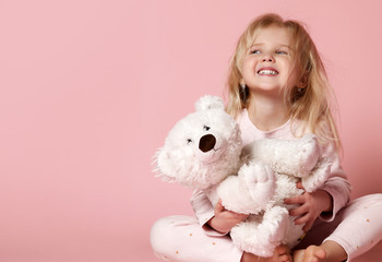 Little baby girl toddler sitting  with white polar teddy bear happy smiling on pink