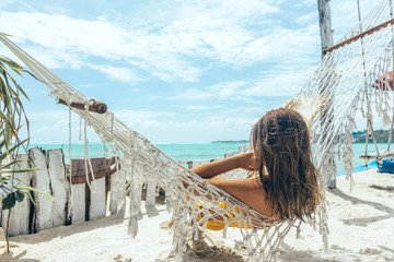 Girl relaxing in hammock in tropical beach cafe Wall mural