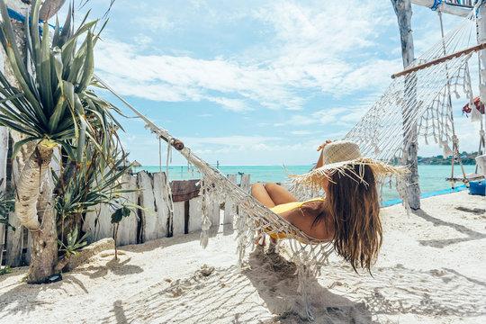 Girl relaxing in hammock in tropical beach cafe