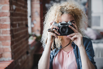Curly blonde woman holding her retro photo camera at home. Wall mural