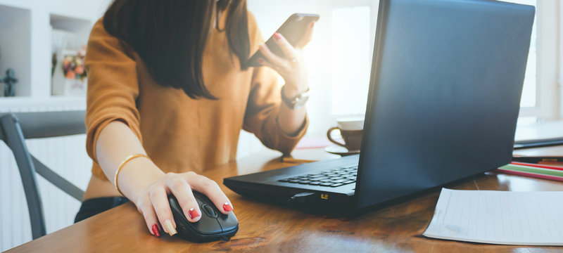 Closeup of hand asian businesswoman using mouse to working with laptop and holding smartphone to connect online