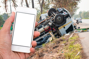 Truck accident. Truck lies on the road after incident. Blank smart phone.