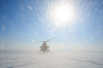 Wall Murals Helicopter Helicopter in the tundra in the Arctic. Polar Aviation. Expeditions, work and travels in the Extreme North. Cold weather. Bright sun and snow. Chukotka, Siberia, Far East of Russia. Place for text.