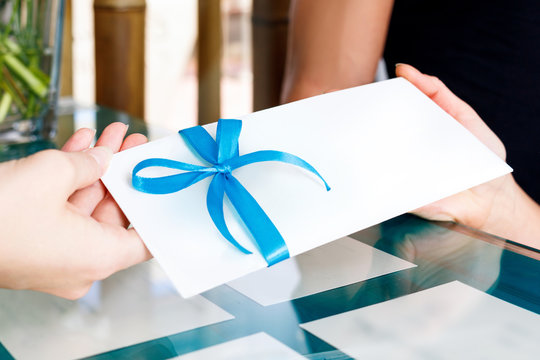 Receptionist woman gives certificate to visit of spa salon.