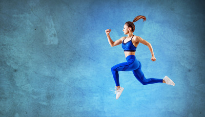 Young woman runner in blue sportswear jump in the air.