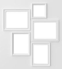 White photo frames on white wall with copy-space