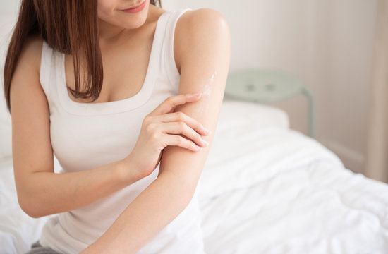 woman applying body lotion on her arm.
