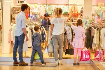 Familie und Kinder gehen in ein Modegeschäft