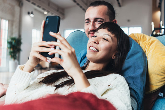 Beautiful couple sitting together and hugging in big loft apartment and using mobile phone