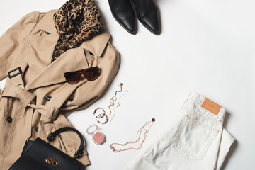 Women fashion clothes and accessories flat lay, beige trench coat with bag, glasses, denim and western boots Wall mural