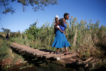 A women carries her baby across a temporary foot bridge after Cyclone Idai in Chipinge