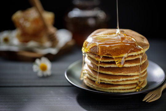 Honey dripping on the stack of pancakes for breakfast on the wooden table, healthy products by organic natural ingredients concept