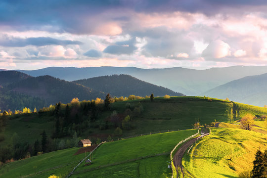 mountainous countryside in evening light. grassy rural fields on rolling hills. wooden fence along the path. mountain ridge in the distance. wonderful weather with pink fluffy clouds
