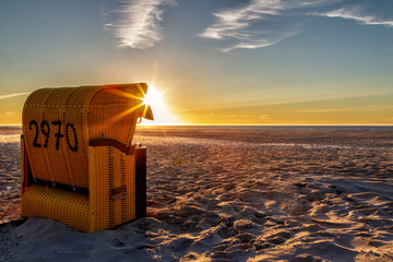 Beach chair on the East Frisian Island Juist in the North Sea, Germany, in evening light before sunset.