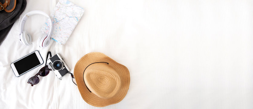 Summer travel items on blanket on bed.Top view of accessories travel (camera,hat,headphone,map ) on bed blankket.prepareing for holiday vacation trip.journey planning.banner for display of design.