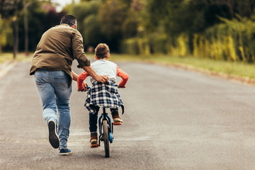 Man helping his kid in learning to ride a bicycle