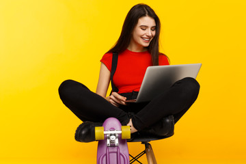 A smiling beautiful brunette young woman with closed eyes, seated on a high chair, holding in hands a laptop, isolated on a yellow background.