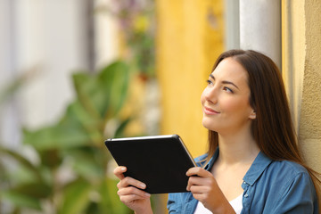 Woman holding a tablet thinking looking at side