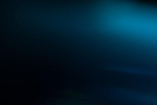 Lens flare effect. Soft defocused blurred light shine on dark blue background