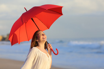 Excited woman holding red umbrella celebrating success