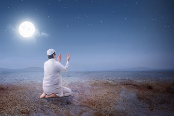 Rear view of asian muslim man sitting in pray position while raised hands and praying on the sand dune Wall mural