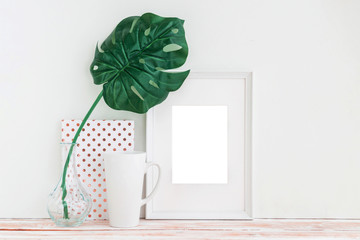 White frame, cup, dotted notebook and green palm leaf in vase on white background with copy space. Mockup.