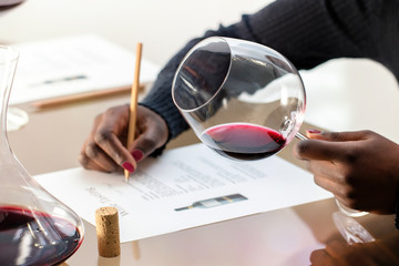 Enologist evaluating red wine at wine tasting.