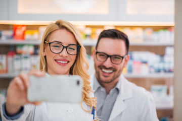 Male and female pharmacist taking a selfie.