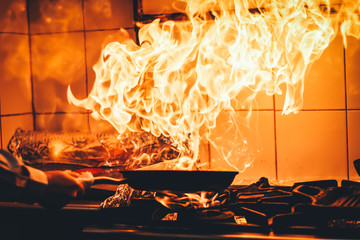 The chef cooking and makes a fire in a pan. Cooking with fire. Crown food. Charismatic chef in the kitchen.