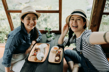 happy japanese friends spending time in Tokyo having fun doing tea ceremony drinking eating cake dessert. women tourist taking selfie in wooden traditional house. smiling female making self portrait.