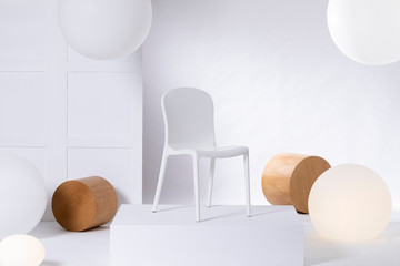 A simple, plastic, white chair standing on a podium against white background. Real photo of furniture presentation in a shop interior