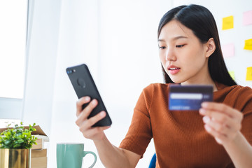 Young beautiful asian woman using smart phone and credit card for shopping online