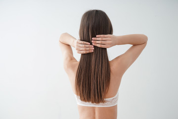 Young woman with beautiful long hair on white background