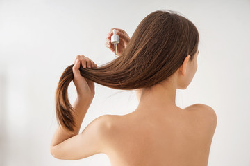 Woman using cosmetics for hair care on white background
