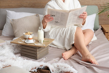 Young woman reading newspaper and having breakfast in bed
