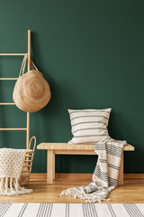 Pillow on wooden stool next to ladder with bag in green living room interior with rug. Real photo