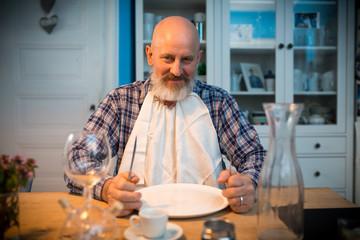 wer kocht ? Mann sitzt vor leerem Teller am Tisch